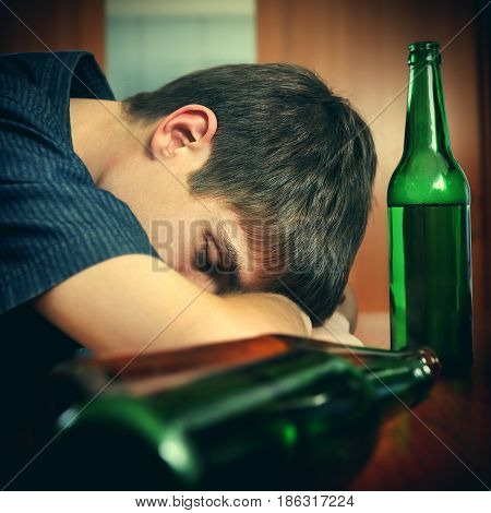 Toned Photo of Tired Young Man sleep with Bottle of the Beer at the Home
