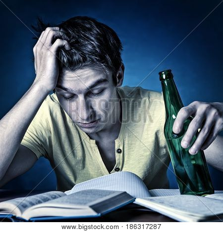 Toned Photo of Tired Student with the Beer on the Blue Background