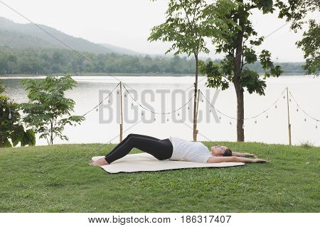 female asian pregnant woman practicing yoga on green grass in public park. concept of prenatal exercise maternity fitness healthy lifestyle and relaxation.