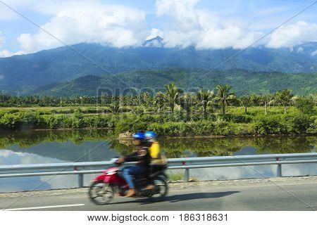 Unidentified people rides motorcycle on a road in Vietnam