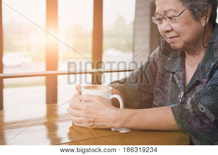 Asian Elderly Woman Sitting And Resting In Cafe Coffee Shop With Cup Of Coffee. Elder Senior Lady In