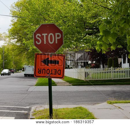 A stop sign with an upside down detour sign affixed to it.