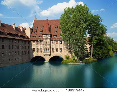 Nurnberg, Germany -Jule 6, 2015:  Hospice of the Holy Spirit (Heilig-Geist-Spital) in the center of Nuremberg on the banks of the Pegnitz river