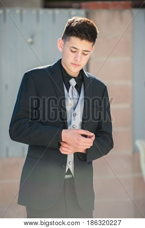 Handsome Mexican teen adjusting cuffs in formal black suit.
