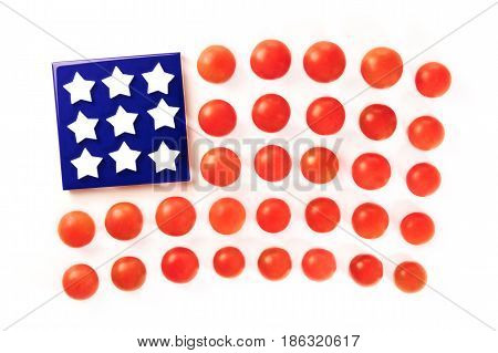 A photo of a representation of the American flag, made up by cherry tomatoes and white stars on a blue coaster, on a white background. A culinary Independence Day greeting card, 4th of July banner