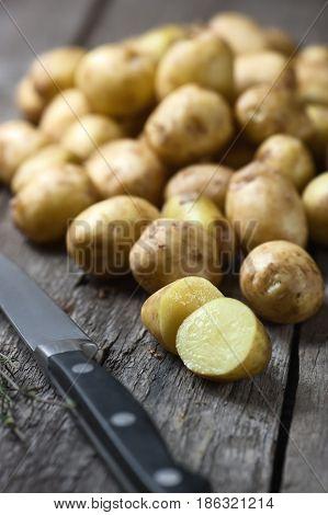 Raw new potatoes on dark wooden cutting board.
