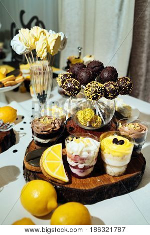 Chocolate Cake Pops, Desserts In Glasses And Cookies On Wedding Candy Bar. Holiday Candy Bar In Yell
