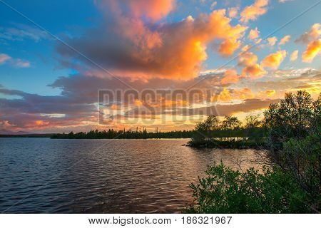 Dramatic sunset in the Arctic. The sun hiding behind the horizon, paints the clouds in a very beautiful color. Fire in the sky over the lake. On the horizon are seen the distant mountains and forest
