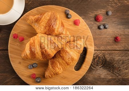 A photo of fresh crunchy croissants with blueberries and raspberries, with a cup of latte and a place for text
