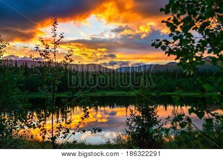 Dramatic sunset in the mountains. The light of the fading day, like a fire in the woods. Very beautiful light and reflection in a forest lake.