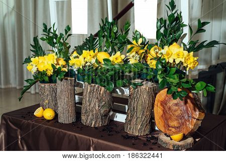 Wedding flower arrangements of yellow daffodils greenery and lemons on stumps under seating plan for wedding reception guests list close-up