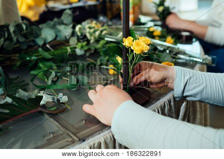 Bunch Of Yellow Roses In Woman's Hands. Florist's Hands Making Flower Composition