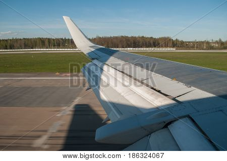 The wing of the aircraft during landing in the background of the runway and the lawn, the position of the flap,