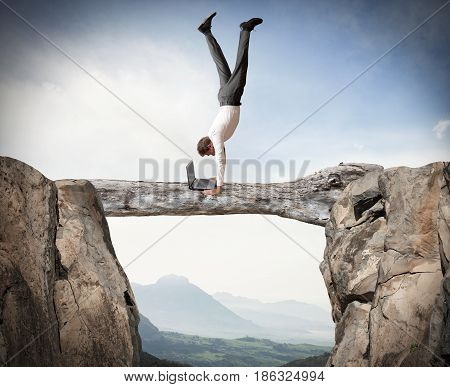 Businessman balancing on a trunk works on pc