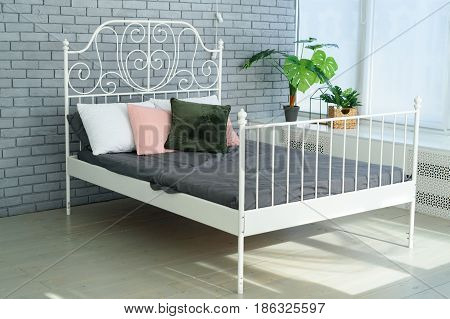 Large White Metal Frame Bed With Decorative Metal Headboard And White, Pink And Green Pillows On It.