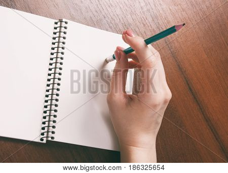 woman hands holding pencil down up rubber eraser book Top View with Copy Space