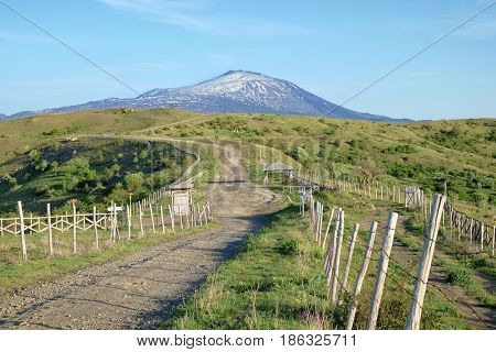 sinuous dirt road to snowy volcanic cone of Etna Mount from Nebrodi Park, Sicily