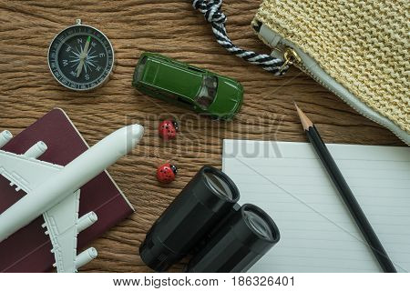 airplane passport compass binoculars pencil paper note and miniature car on wood table as travel planning road trip concept.