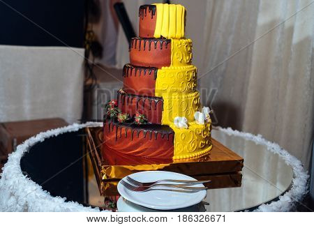 Round Multi Tiered  Yellow And Brown Wedding Cake With Strawberries, Roses And Chocolate Icing. Plat