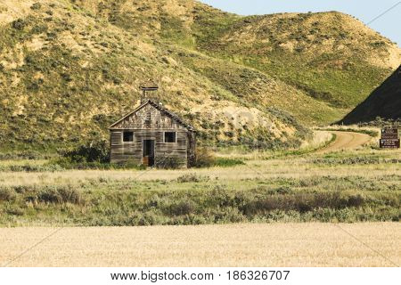 Abandoned wooden school house building in rural countryside. Central Montana USA.