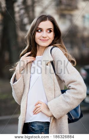 Emotion portrait of smiling happy woman with wavy hair, make up, stylish wearing in beige coat with leather bag. Beautiful girl looking away over shoulder, walking at spring park.