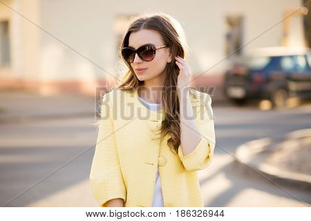 Portrait of fashionable and stylish young beautiful woman in sunglasses posing and walking on street, touching face and hair.Girl in yellow coat, with long wavy hair looking away. Spring street look.