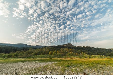 Puffy clouds in a blue sky over green and rocky landscape in the Columbia River Gorge Washington USA.