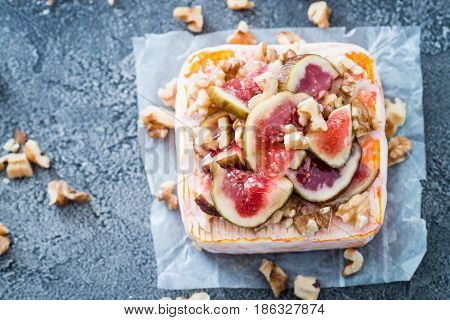 Raw French Soft Cheese From Brittany Region Covered With Chopped Figs, Walnuts And Honey On Dark Bac