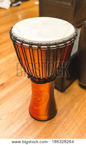 African percussion instrument or djembe on wood floor.
