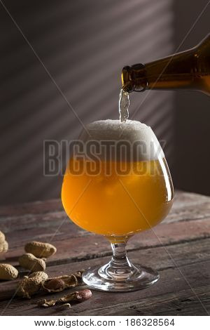 Detail of a glass of cold unfiltered pale beer being poured from a bottle with some peanuts next to the glass. Selective focus