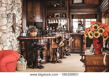 Custom made wood bar with saddle seats and various decorations inside a lavish cabin.