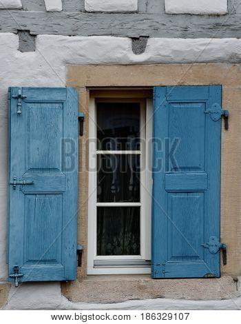 Window with half open blue wooden shutters