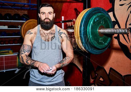 Young Muscular Bearded Tattooed Man With Coated Hands In Powder Chalk Magnesium In Gym. Ready For Wo