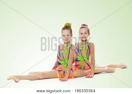 Two adorable little twin girls, gymnastics in the sports school. Girls beautiful gymnastic leotards. They do the splits.On a light green gradient background.