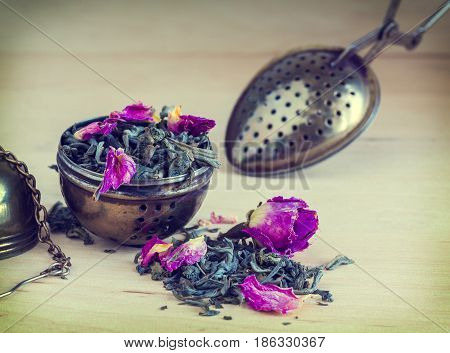 tea strainer closeup tea leaves and rose buds selective focus retro style