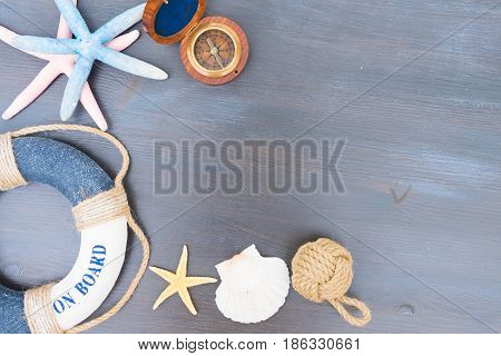 Old vintage compass with marine knot, life-ring and seastars with copy space on wooden table