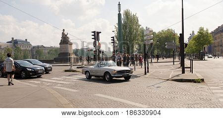 ParisFrance-April 292017:According to the Quai Voltaire moving peoplecyclists and cars.Men crossing the road on the transition