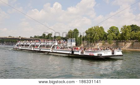 ParisFrance- April 292017:On the Seine a ship sails with tourists who inspect the sights and photograph them