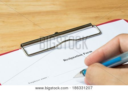 Resignation form with hand hold the pen for filling on wood desk background