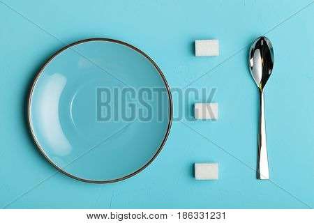 Spoon saucer and sugar cubes on turquoise background, the view from the top with place for your text. Conceptual food photos