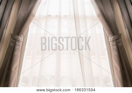 Opened silk curtain in cream color on bright window covering by see through white curtain moving by blowing wind.