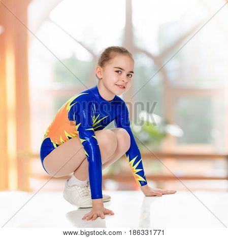 Beautiful Russian girl gymnast younger school age, in blue in a sports swimsuit.The girl squatted down and put her hands on the floor.In the sports hall with mirror and a large semi-circular window.