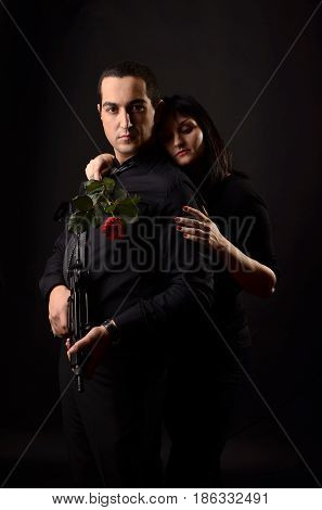 Young Woman With Red Rose Hugs Man In Black Shirt With Gun In His Hands. Love Story On Black Backgro