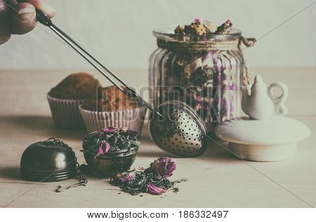 Tea strainer closeup tea leaves and rose buds glass jar selective focus retro style