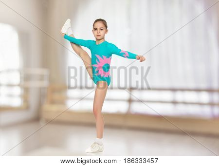 Very flexible little girl gymnast, junior school age, in a beautiful gymnastic swimsuit turquoise.She lifted her foot and took her hand.In the sports hall with mirror and a large semi-circular window.