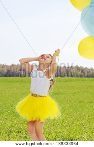 Pretty little blonde girl in a short bright yellow skirt and white blouse.Girl holds in hands balloons , She looks at them from the bottom up.On the background of green grass and blue sky with clouds.