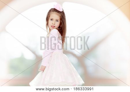 Dressy little girl long blonde hair, beautiful pink dress and a rose in her hair.She turned sideways to the camera and folded his hands in front of him.In a room with a large semi-circular window.