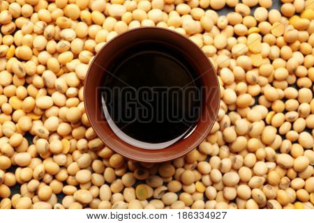 Bowl with tasty soy sauce and beans, closeup