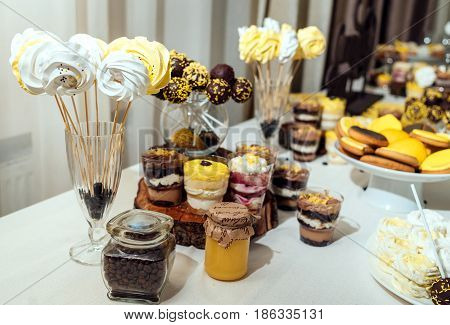 White And Yellow Meringues On Stick In Glass With Coffee Beans On Holiday Candy Bar In Blur