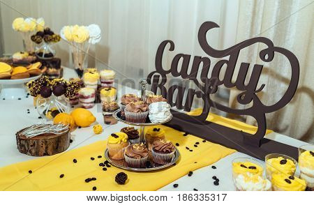 Holiday Candy Bar. Candy Bar Served With Cupcakes With Chocolate And Lemon Cream On Stump And Others